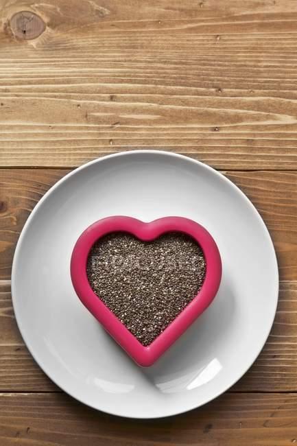 Vista superiore di semi di Chia in ciotola a forma di cuore su superficie di legno — Foto stock