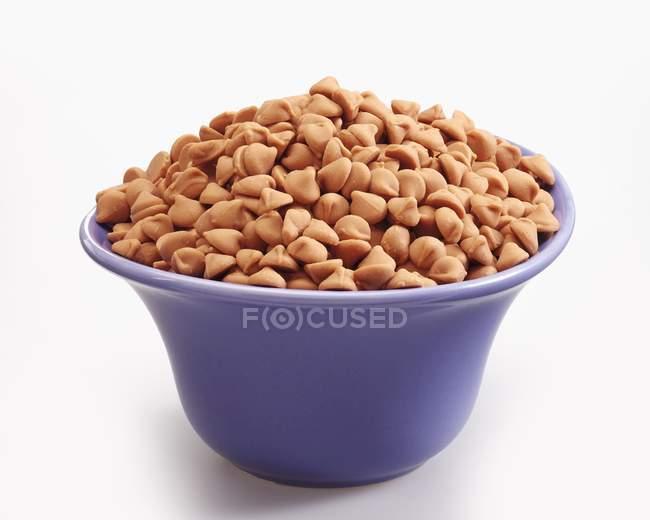Vue de caramel chips dans un bol bleu — Photo de stock