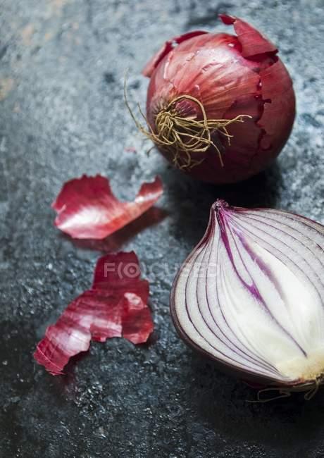 Красный лук, цельный и наполовину — стоковое фото