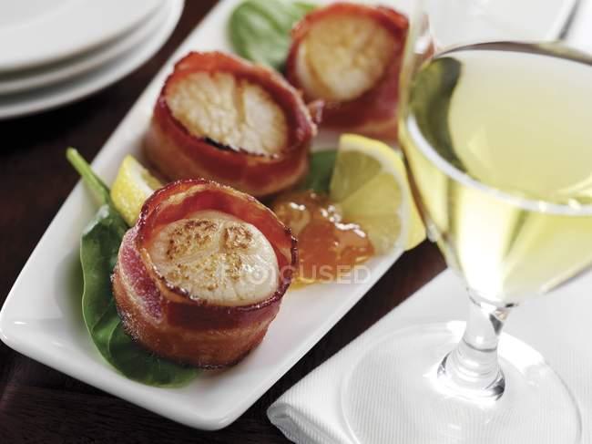 Primo piano vista di pancetta avvolto capesante su piatto con bicchiere di vino bianco — Foto stock