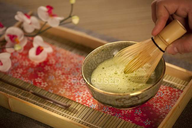Closeup view of hand mixing Japanese Matcha green tea in a ceremonial bowl with whisk — Stock Photo