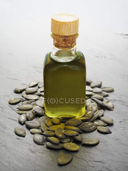 Vista del primo piano di olio di semi di zucca e semi di zucca su superficie grigia — Foto stock