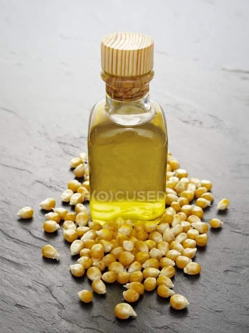 Corn oil and corn kernels — Stock Photo