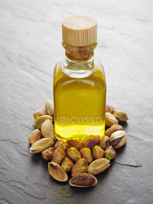 Pistachio oil and pistachios — Stock Photo