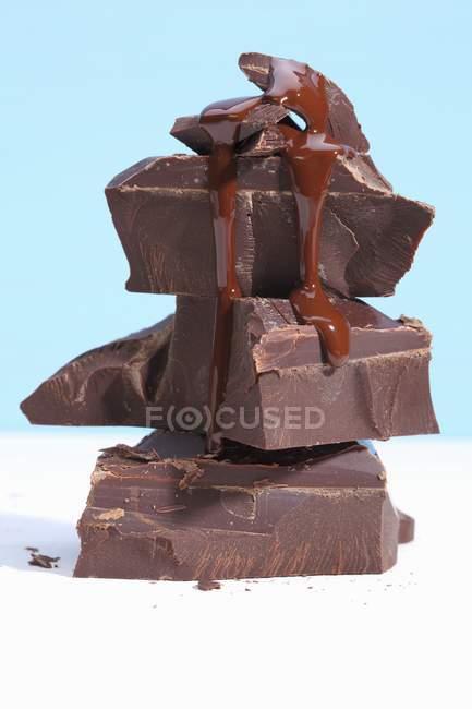 Розплавленого шоколаду капає вниз частини шоколаду — стокове фото