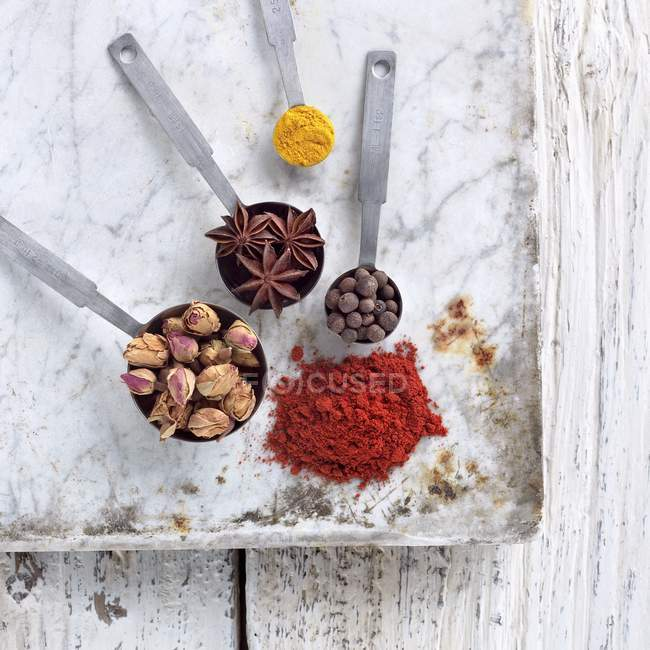 Top view of spice mix in measuring spoons and on marble board — Stock Photo
