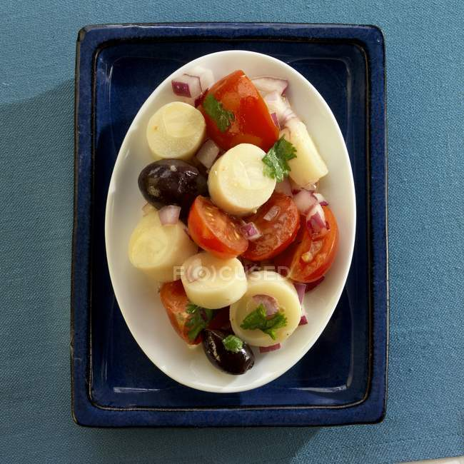 Top view of Brazilian hearts of palm salad with tomatoes, olives and onion — Stock Photo