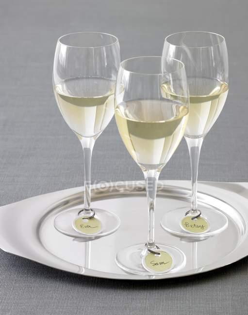 Vasos de vino blanco con etiquetas de nombre - foto de stock