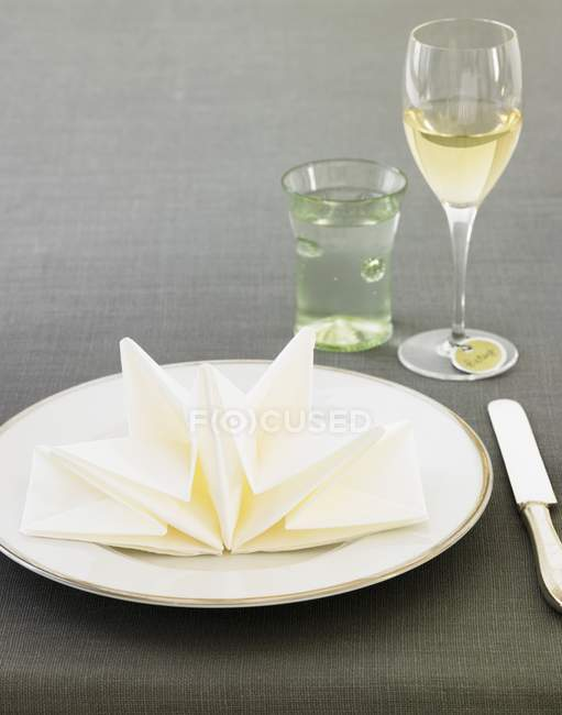 Closeup view of place setting with decoratively folded napkin, water and white wine — Stock Photo