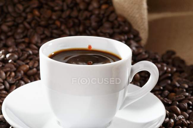 Drops of coffee falling into cup — Stock Photo