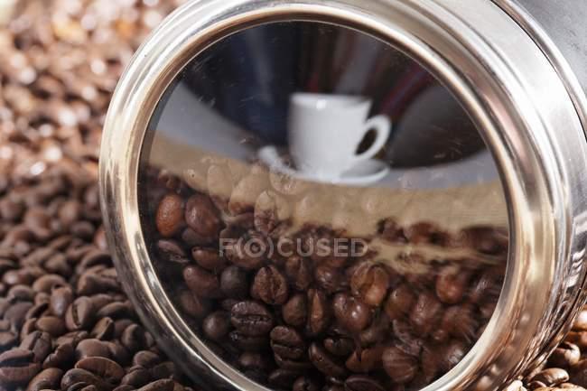 Taza y café frijoles montón reflejado en la superficie de metal estaño - foto de stock