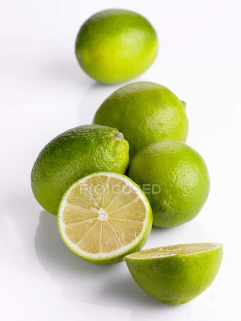 Fresh ripe limes with halves — Stock Photo