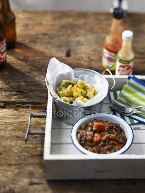 Side dishes for a barbecue:battered okra and baked beans on wooden surface — Stock Photo