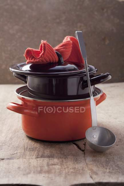 Closeup view of piled pots with lid, ladle and pot holder — Stock Photo