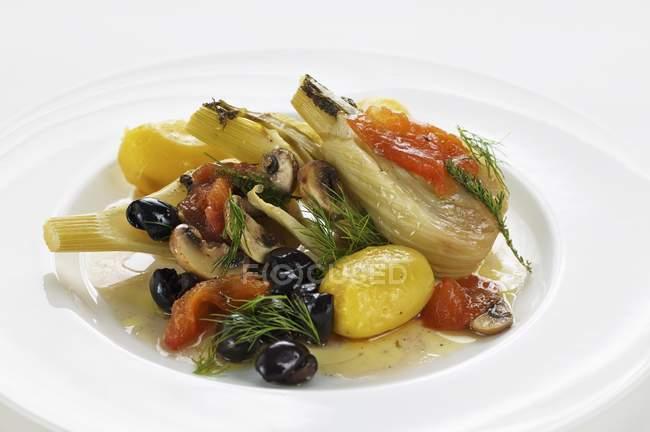 Finocchio avvolto in un foglio cotto con olive, pomodori e patate su piatto bianco — Foto stock