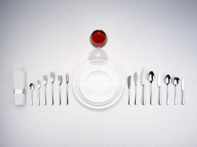 Top view of plates with cutlery, a napkin and a glass of red wine — Stock Photo