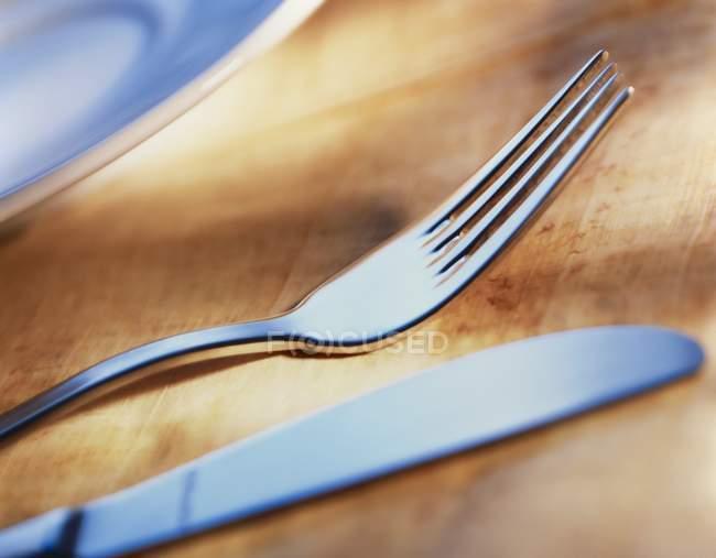 Primo piano vista di coltello e forchetta su superficie di legno — Foto stock