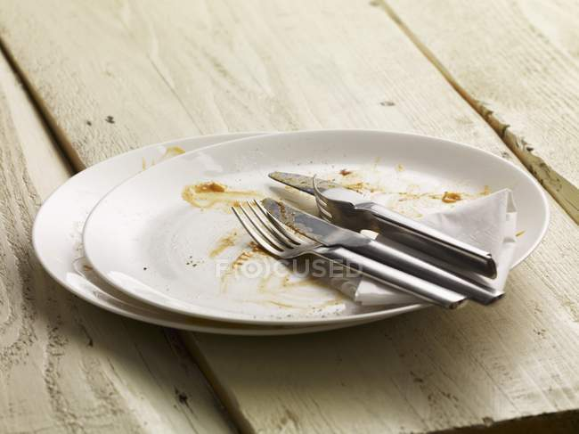 Closeup view of dirty plates with cutlery and a paper napkin — Stock Photo