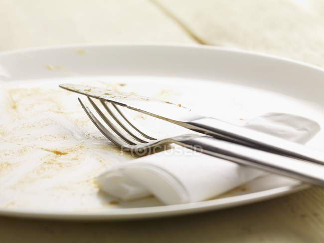 Closeup view of dirty plate with cutlery and paper napkin — Stock Photo