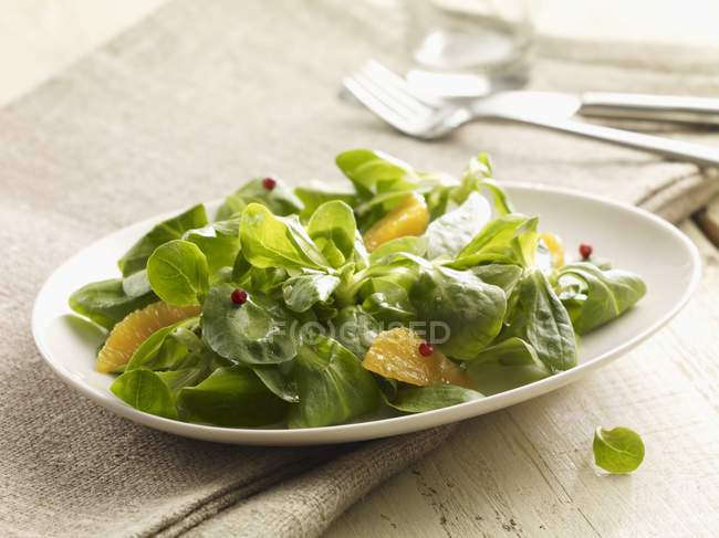 Closeup view of lettuce leaves with orange wedges — Stock Photo
