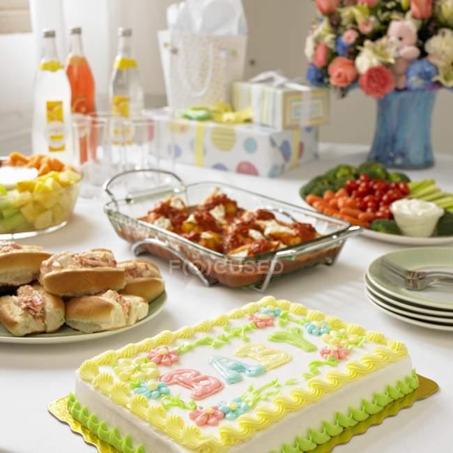 Повышенные мнение ребенка слова на торт с различных блюд и напитков на столе — стоковое фото