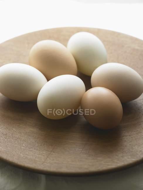 Свежие белые и коричневые яйца — стоковое фото