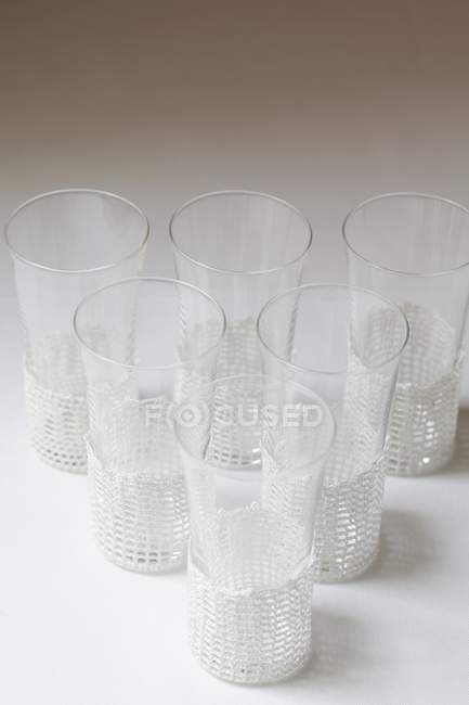 Elevated view of glasses with holders arranged in a triangle — Stock Photo