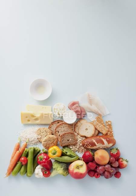Vista superior de varios grupos de alimentos en la superficie blanca - foto de stock