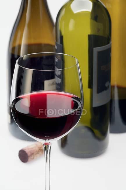 Стакан красного вина и пробки — стоковое фото
