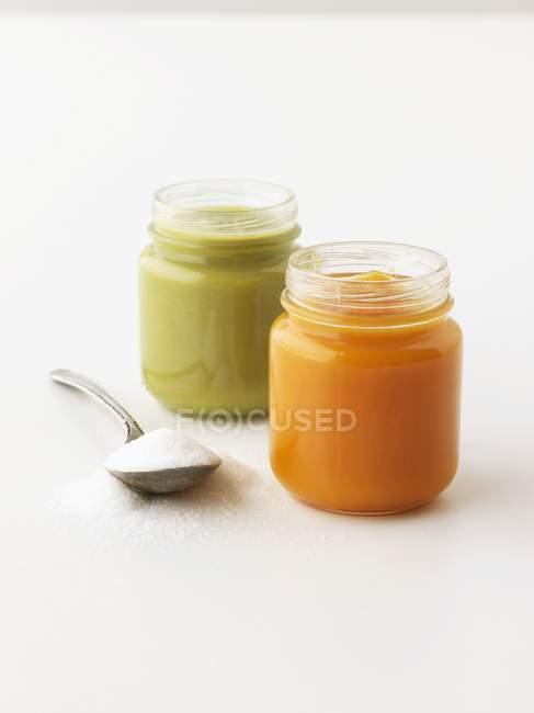 Крупним планом вид на дві банки овочевими пюре і ложку цукру — стокове фото