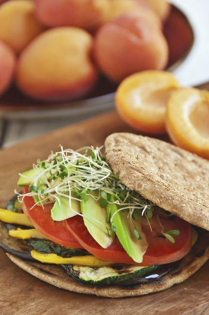 Veggie Sandwich with Grilled Eggplant, Zucchini, Yellow Peppers, Tomato and Avocado on a Flat Round Roll — Stock Photo