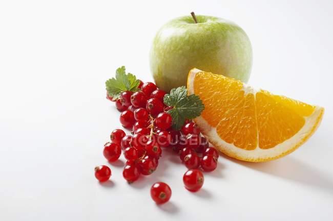 Красная смородина с апельсиновым клином и яблоком — стоковое фото