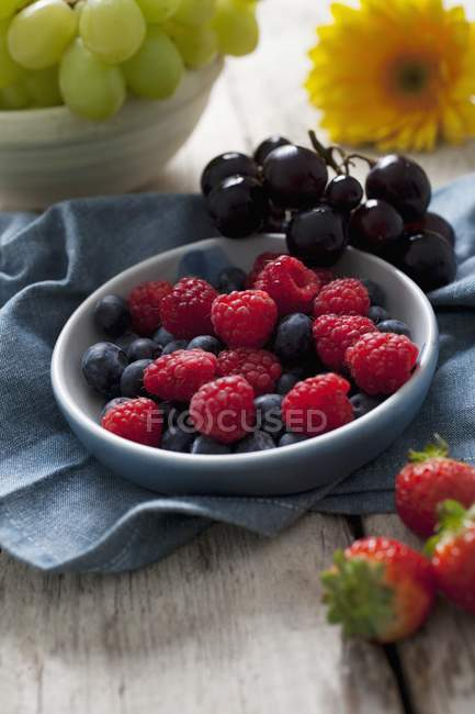 Raspberries and blueberries with grapes — Stock Photo