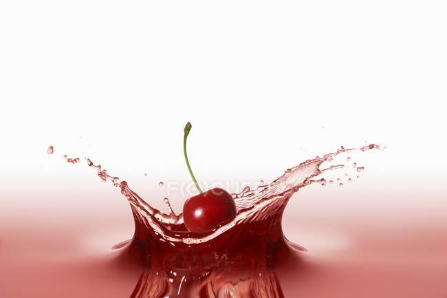 Cherry falling into red juice — Stock Photo