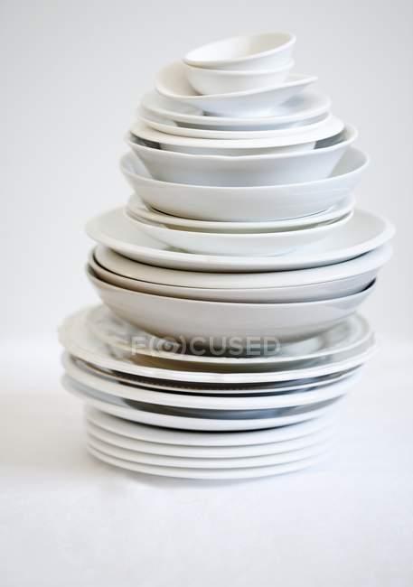 Vista de primer plano de una variedad de platos apilados en la superficie blanca - foto de stock