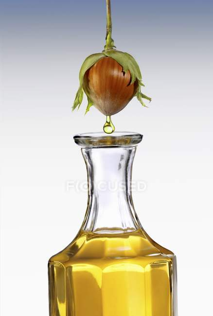 Closeup view of hazel nut oil dropping from a hazel nut into a carafe — Stock Photo