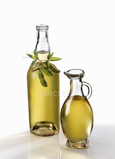 Huile de soja en bouteille et carafe sur fond blanc — Photo de stock