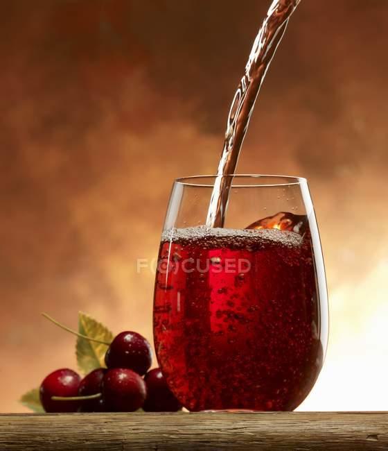 Pouring cherry juice — Stock Photo