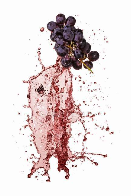 Red grapes with wine splash — Stock Photo