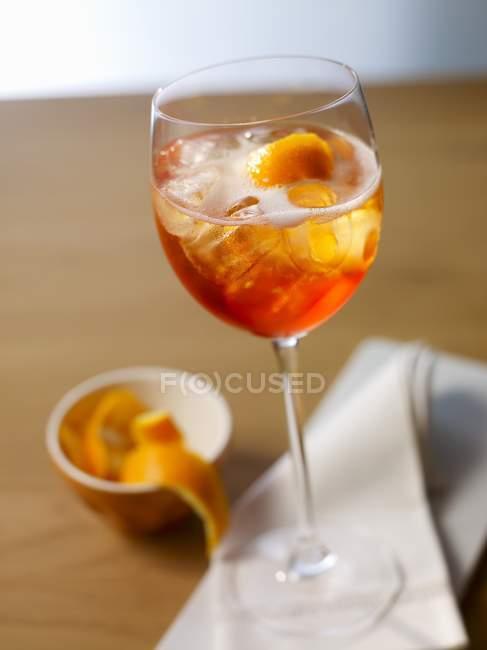 Nahaufnahme von Aperol Spritz mit Eis und Orangenschalen in Tulpenglas — Stockfoto
