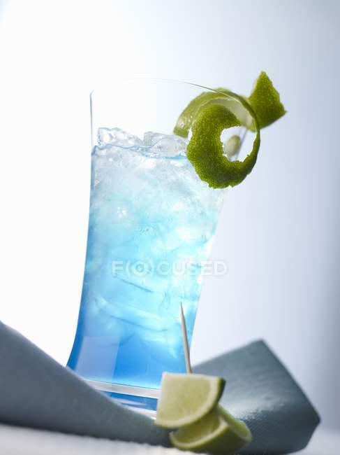 Nahaufnahme von Blaulicht-Eiscocktail mit Limettenschalen und -stücken — Stockfoto
