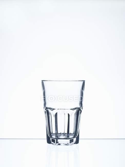 Крупним планом подання одну склянку з водою залишається на білій поверхні — стокове фото