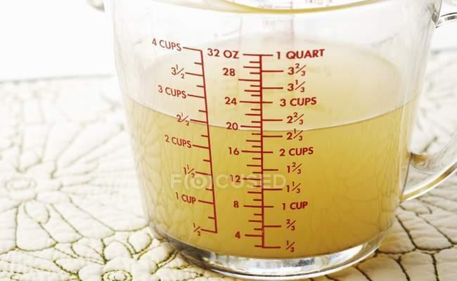Vista de cerca del caldo de pollo en una taza de medir - foto de stock