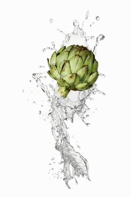 Artichoke with splash of water — Stock Photo