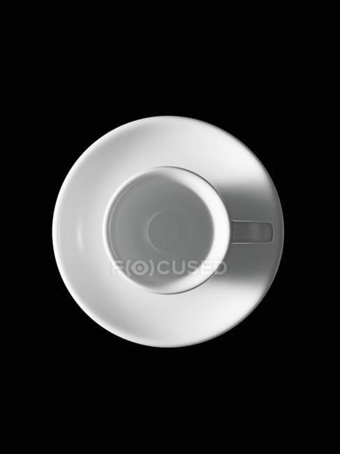 Closeup top view of white Espresso cup on saucer and black background — Stock Photo