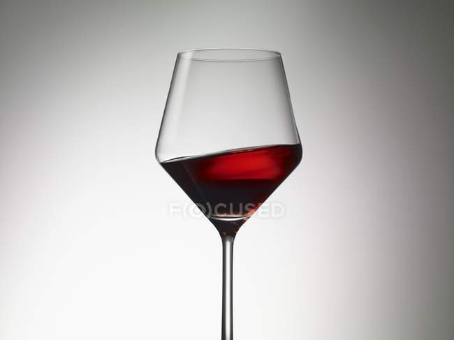 Red wine sloshing in a wine glass — Stock Photo