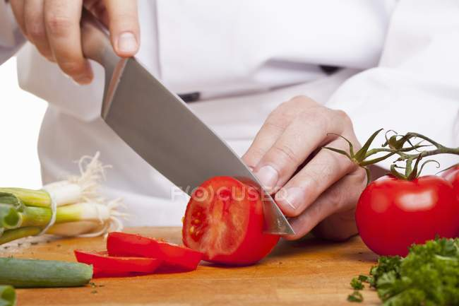 Chef Slicing red tomatoes — Stock Photo