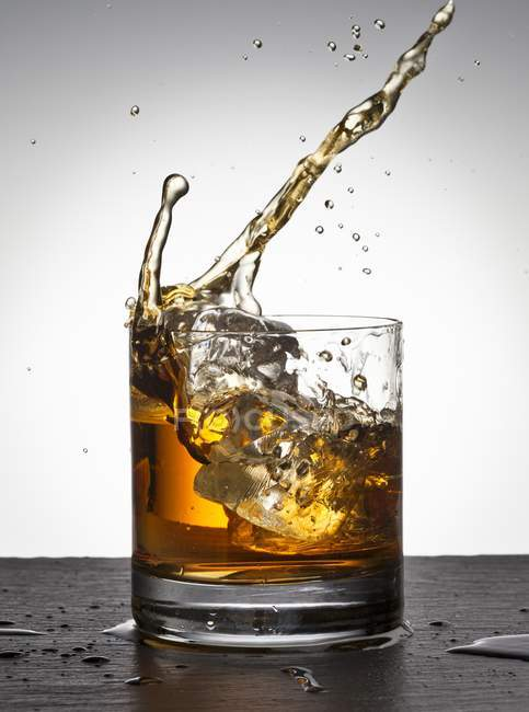 Ice cubes falling into whisky — Stock Photo