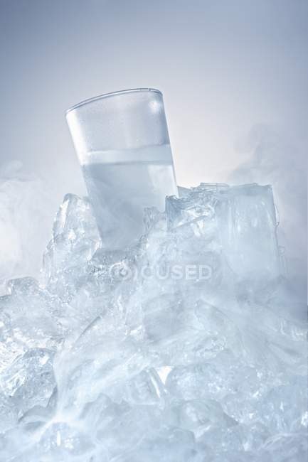 Vodka glass in a block of ice — Stock Photo