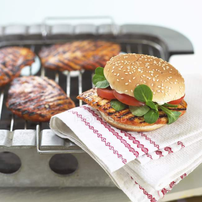 Closeup view of grilled chicken burger on towel — Stock Photo